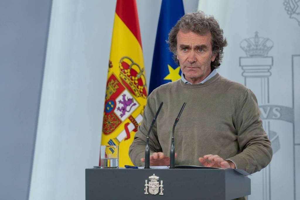 Fernando Simón fala à imprensa diante de um microfone, com a bandeira da Espanha e da União Europeia detrás