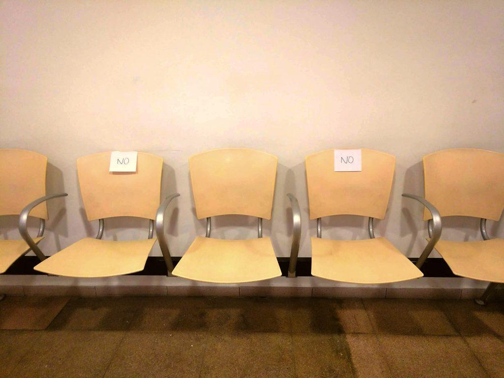 """Cadeiras vazias em sala de espera de hospital com cartazes alternados com os dizeres """"não"""""""