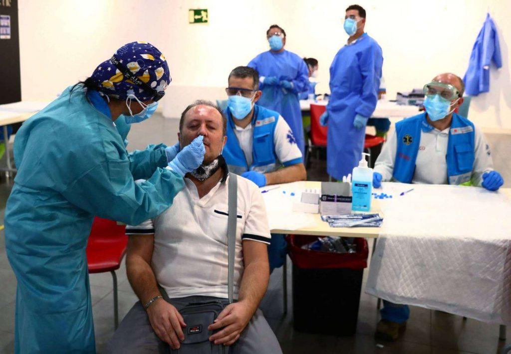 Homem é submetido a teste PCR, rodeado de enfermeiros e assistentes